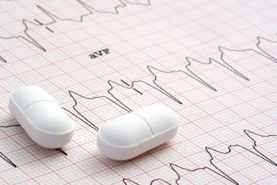 white pills lying on a chart showing heart rate patterns