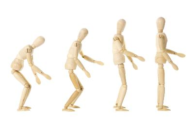 four wooden figures in a row progressively standing up straight