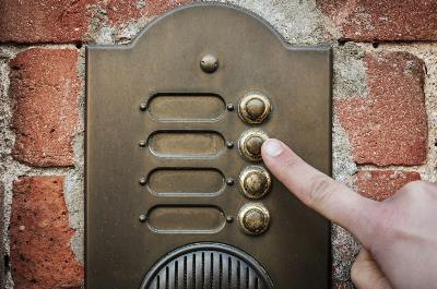 finger reaching out to old fashioned doorbell