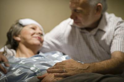 ailing woman in bed with bandage on her head, man looking at and embracing her, both smiling