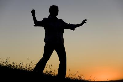 Shadowy figure doing Tai Chi against sunset background