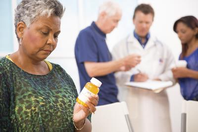Woman looking at medicine while team discuss her case