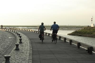 Couple bike riding on a long path by the water