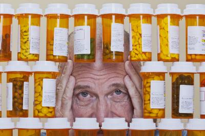 Senior man with an unhappy, confused expression looking through an opening in rows of prescription medication.