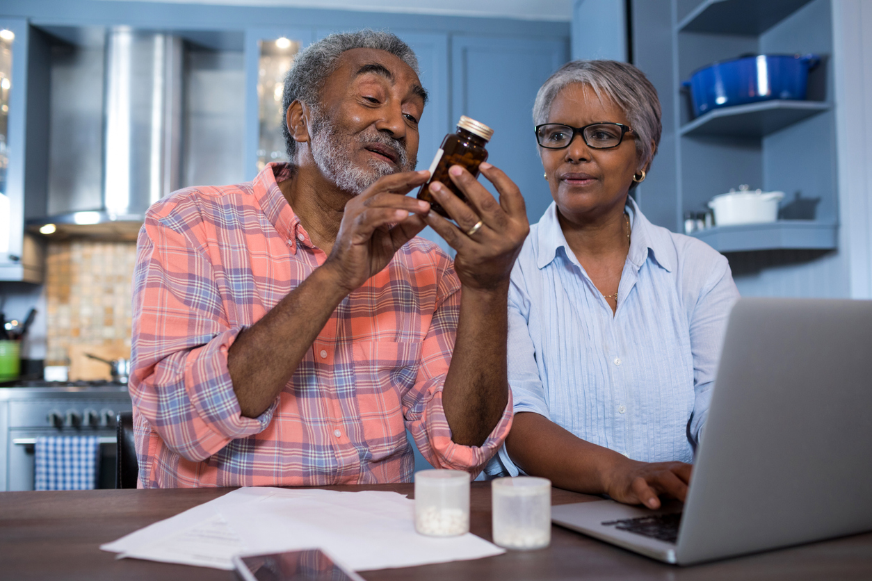Elderly couple sitting in their kitchen. The husband holds up a bottle of supplements as he reads it, while his wife stares at the bottle and types on her laptop.